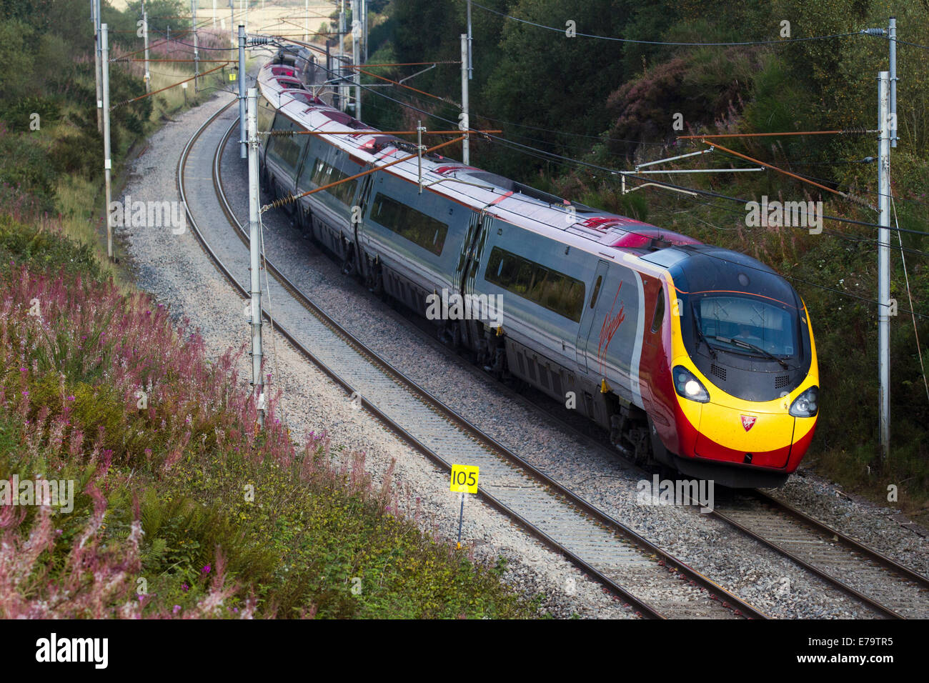 Power lines, and gantries for electric trains   British Railways carriages descending Virgin Voyager Train at Shap, Stock Photo