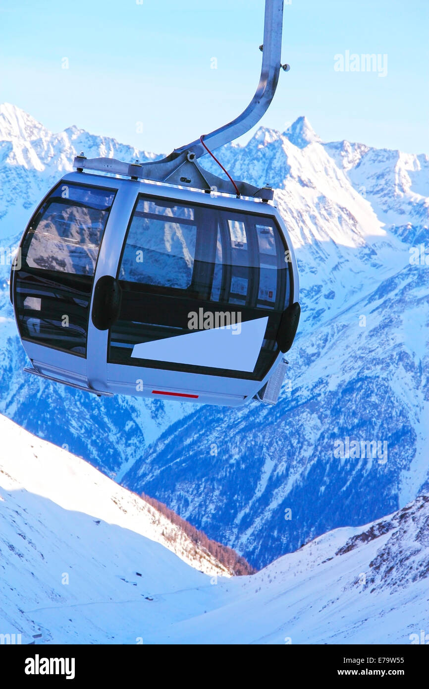 Ski lift chairs on bright winter day in Alp mountains - Stock Image