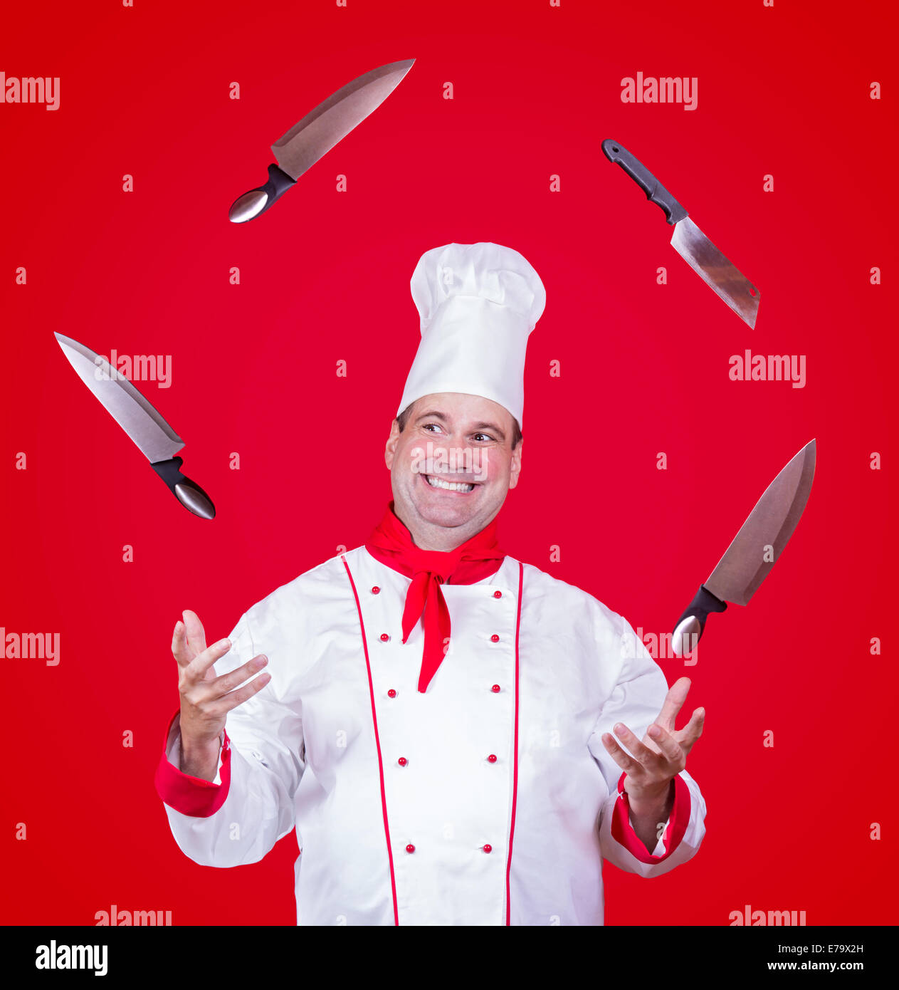 cheerful cook juggle with knife - Stock Image