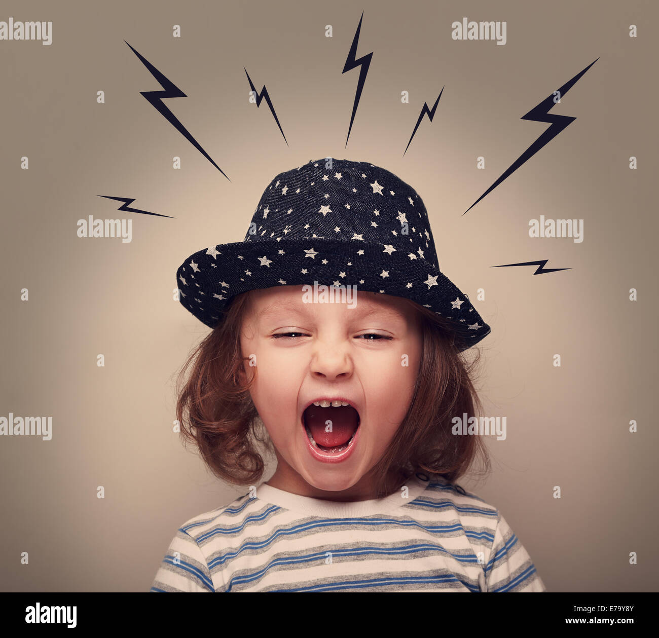 Angry shouting kid with lightnings above the head on grey background - Stock Image