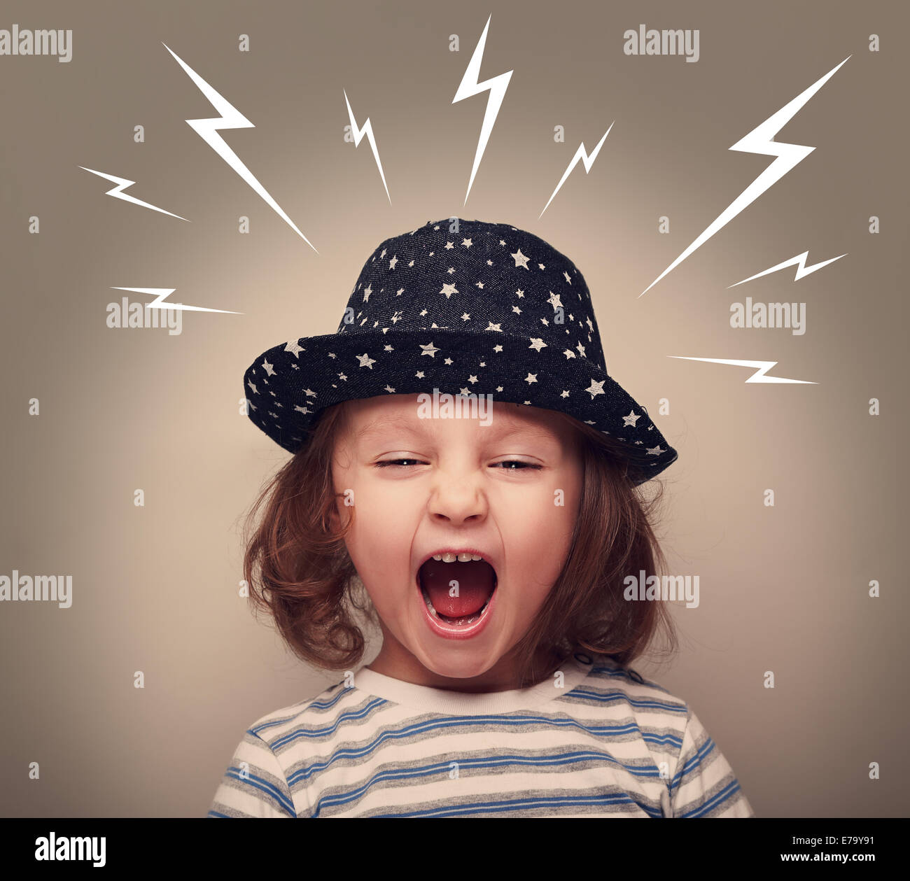 Angry kid in hat screaming with open mouth and white lightnings above on dark background - Stock Image