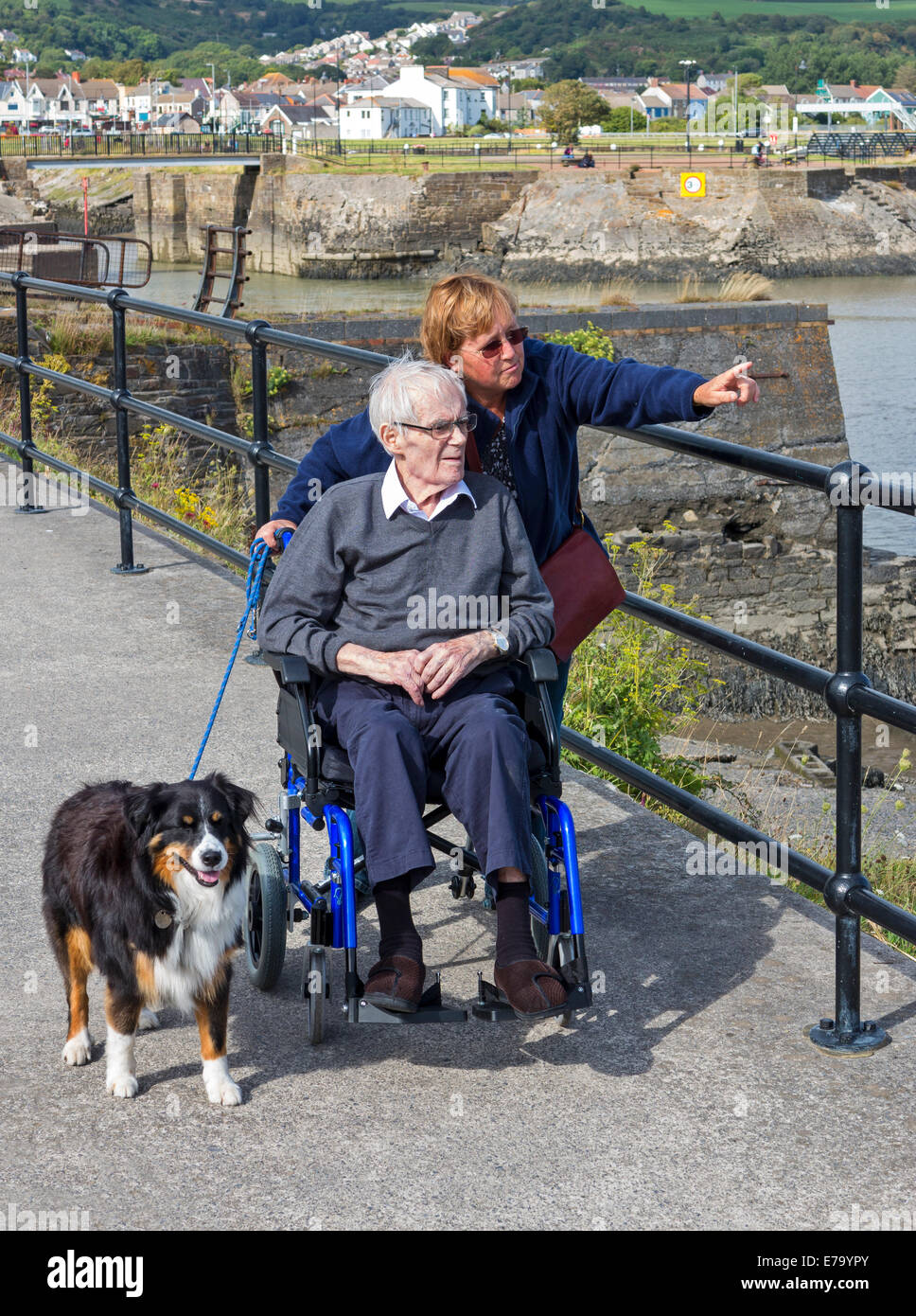 A daughter pointing out the sights of the harbour at Burry Port, Wales, to her elderly disabled father in a wheelchair - Stock Image