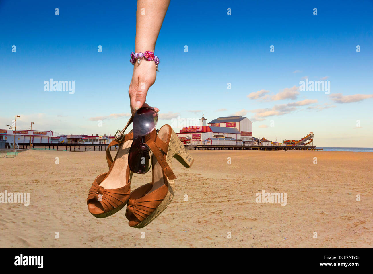 woman carrying shoes on a beach at Great Yarmouth, UK - Stock Image