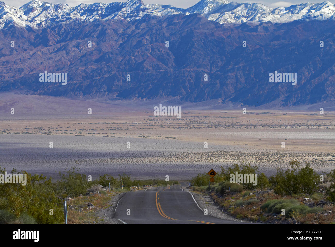 State Route 190 climbing up from Death Valley over Panamint Range, with snowy Grapevine Mountains in background, Stock Photo