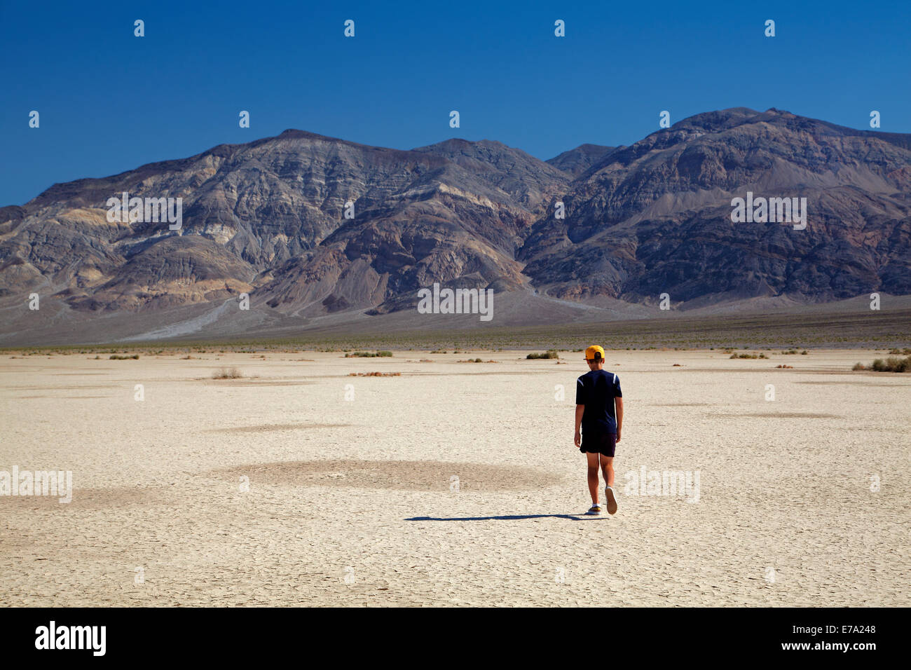 Boy on Salt Pan, Panamint Valley, and Panamint Range, Death Valley National Park, Mojave Desert, California, USA - Stock Image