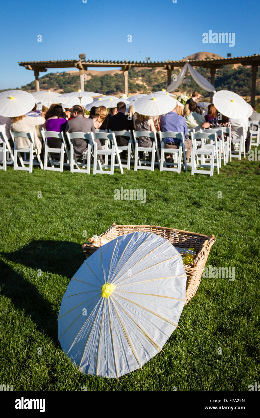 Shade parasols offered for guests to protect themselves from the sun at an outdoor wedding event in California - Stock Image