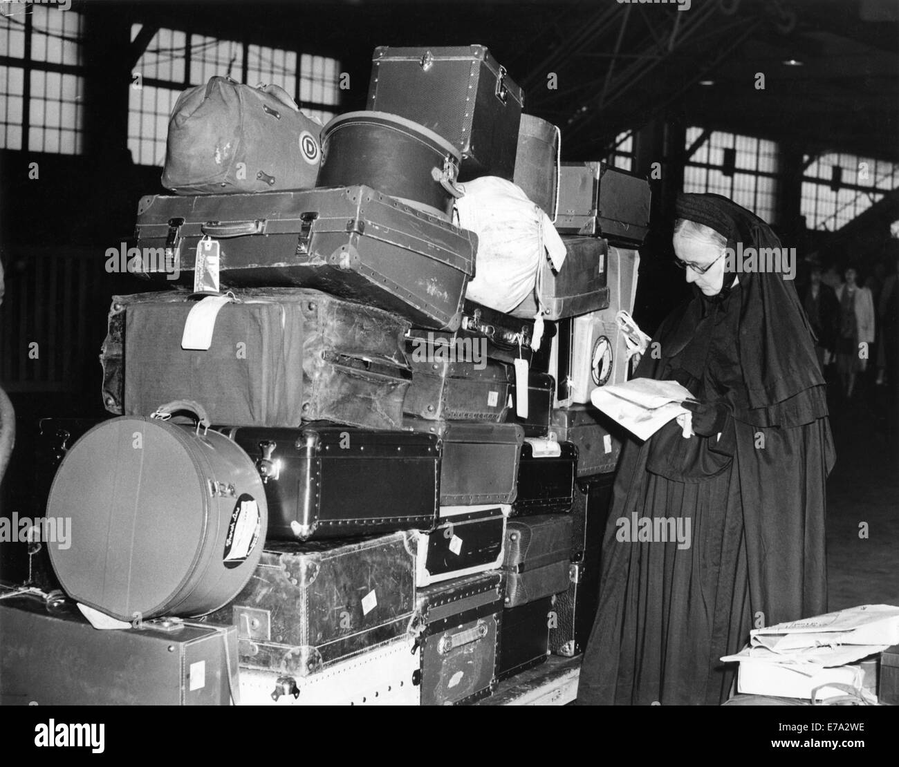 Roman Catholic Sister with Luggage Waiting  to Board SS Normandie While Ship is Being Inspected due to Pending War - Stock Image