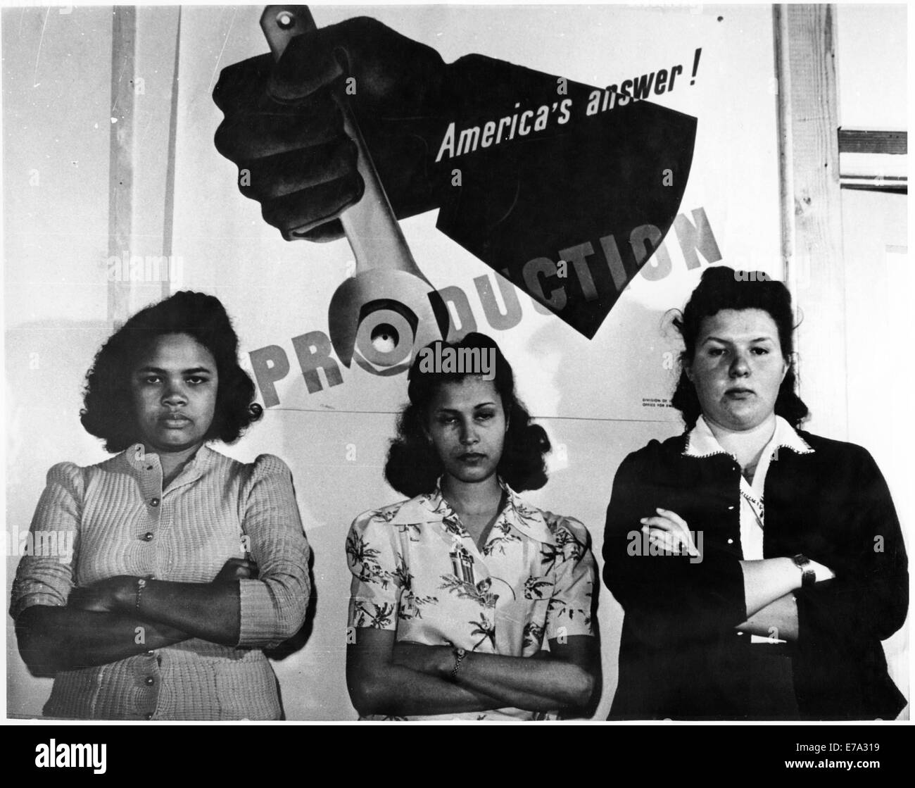 Three Female Factory Workers Standing in Front of 'America's Answer! Production' Poster during World - Stock Image