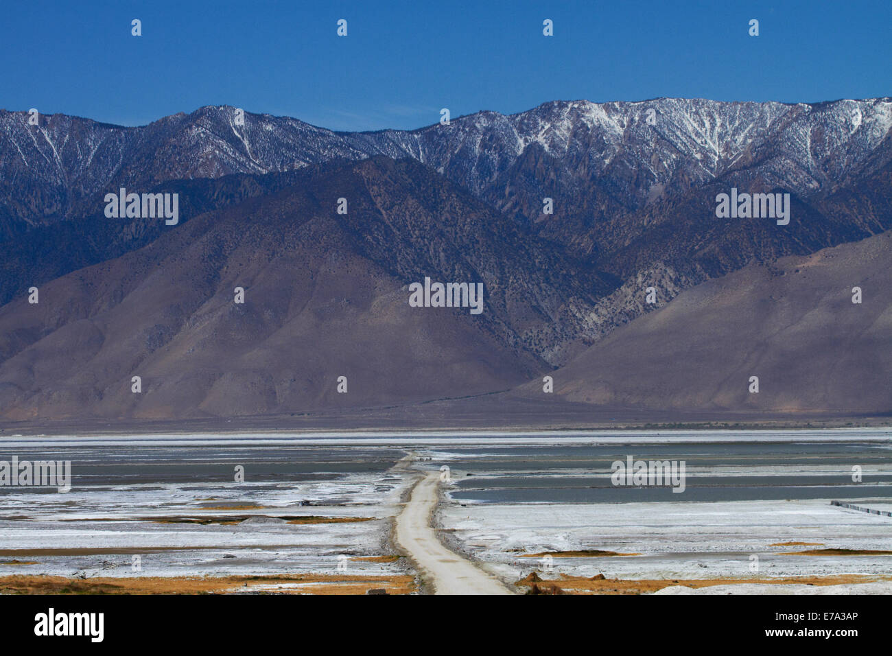 Sulfate Road across Owens Lake (mainly dry salt lake), Owens Valley, and Sierra Nevada Mountain Range, California, - Stock Image