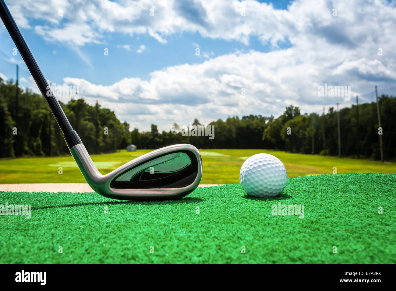 Close-up of a golf ball and a golf iron on a driving range - Stock Image
