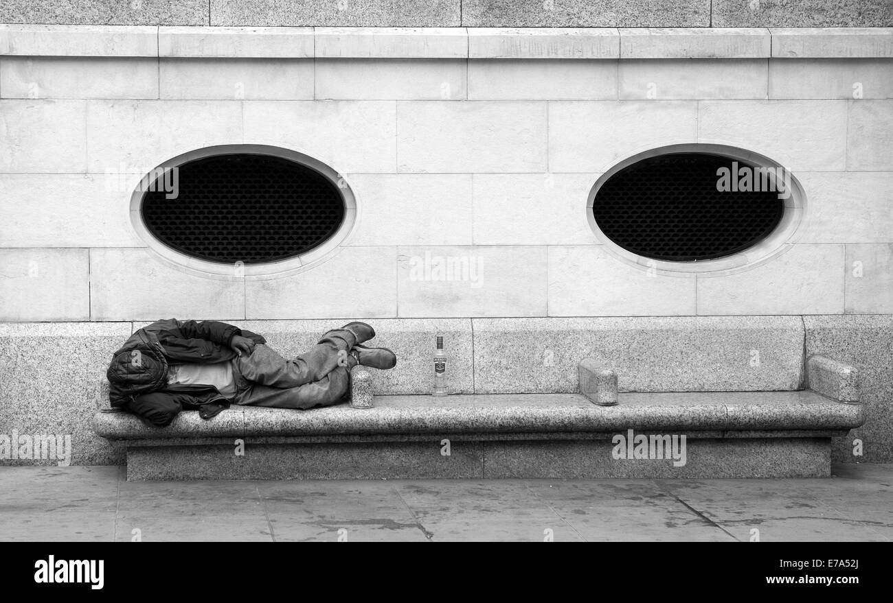 A homeless person asleep on a bench - Stock Image