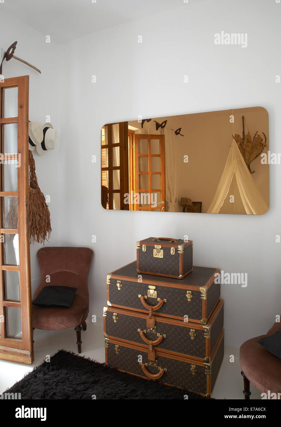 b111d15aeeeb Home interior with two chairs and four Louis Vuitton trunks on the floor