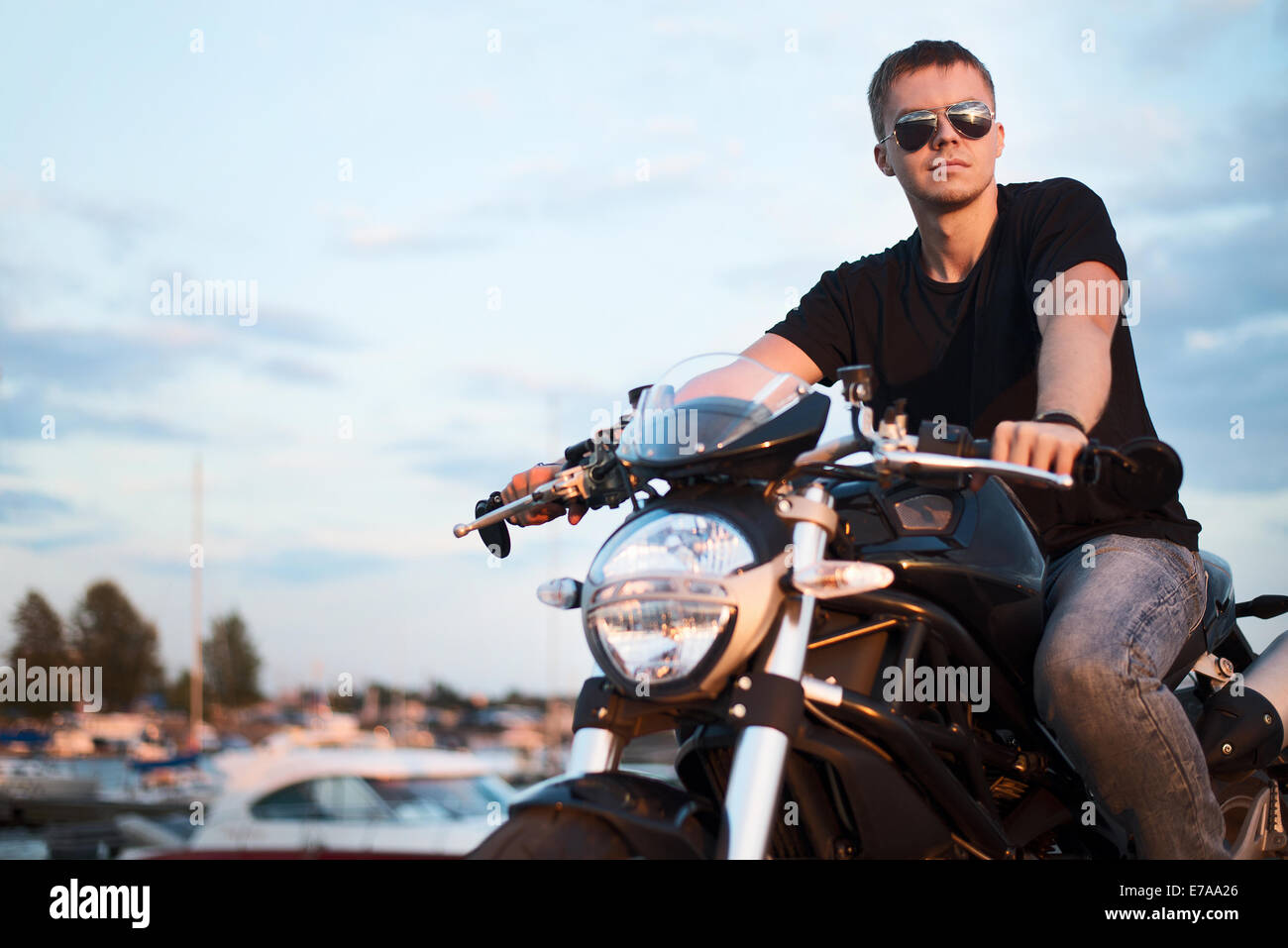 Romantic portrait handsome biker man in sunglasses sits on a bike on a sunset near lake and yacht club. copy space - Stock Image