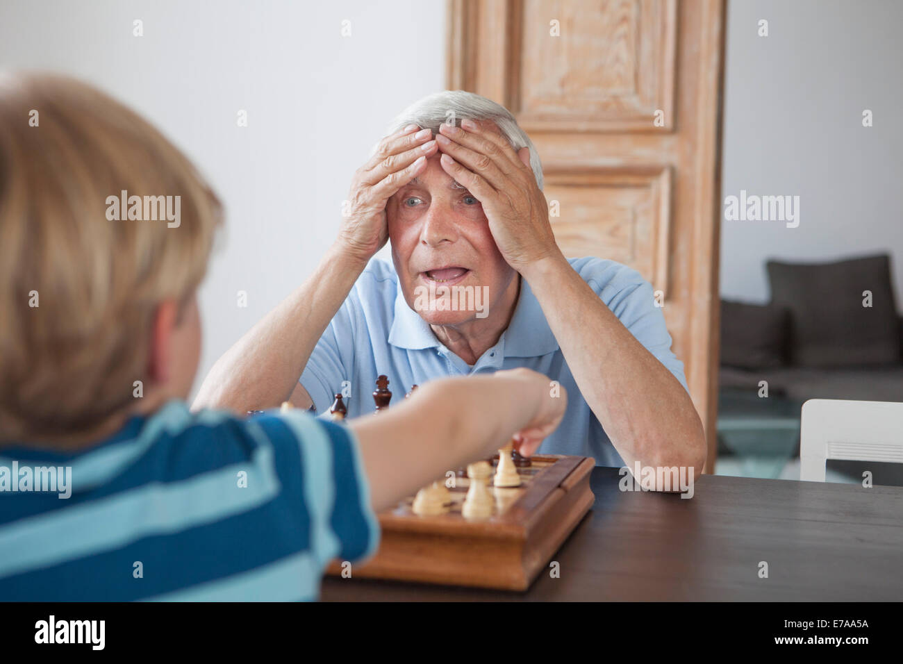 Shocked senior man with head in hands looking at grandson while playing chess at home - Stock Image
