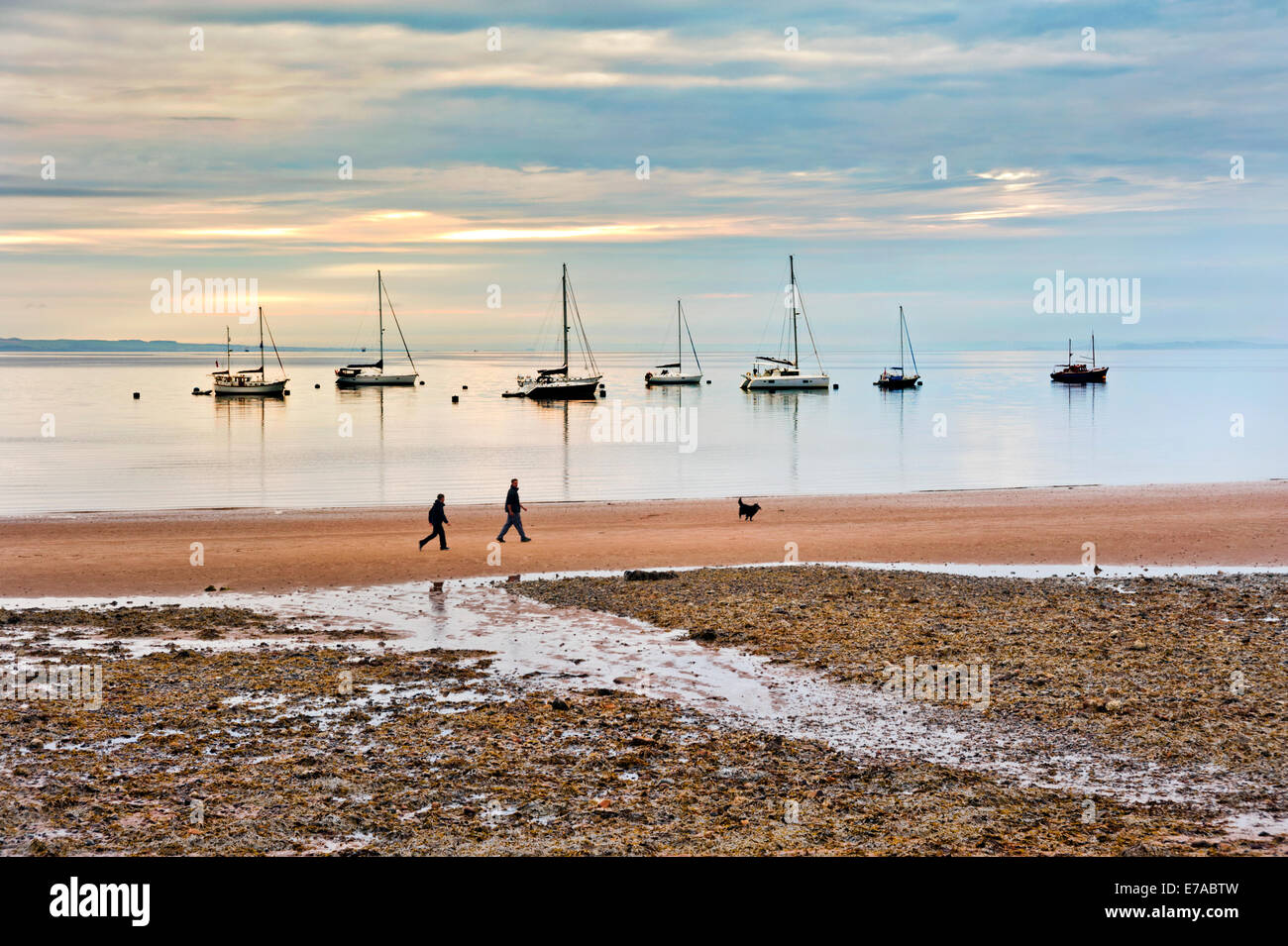 Early morning on the beach at Brodrick, Isle of Arran, Scotland, with dog walkers. - Stock Image