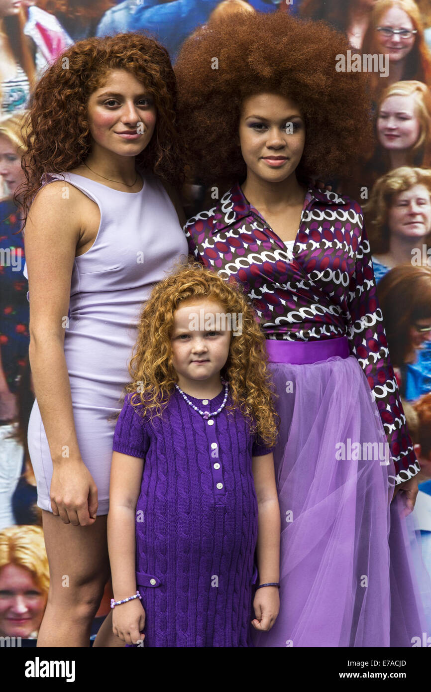 Two women and a girl, all with different red hair, pose for a portrait during the festival of redheads. - Stock Image