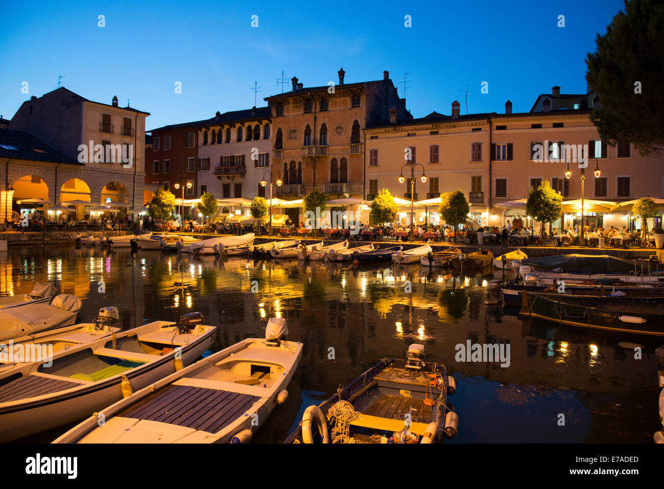 The restaurants of Desenzano del Garda cluster around the the pretty harbour and once the sun sets can become quite - Stock Image