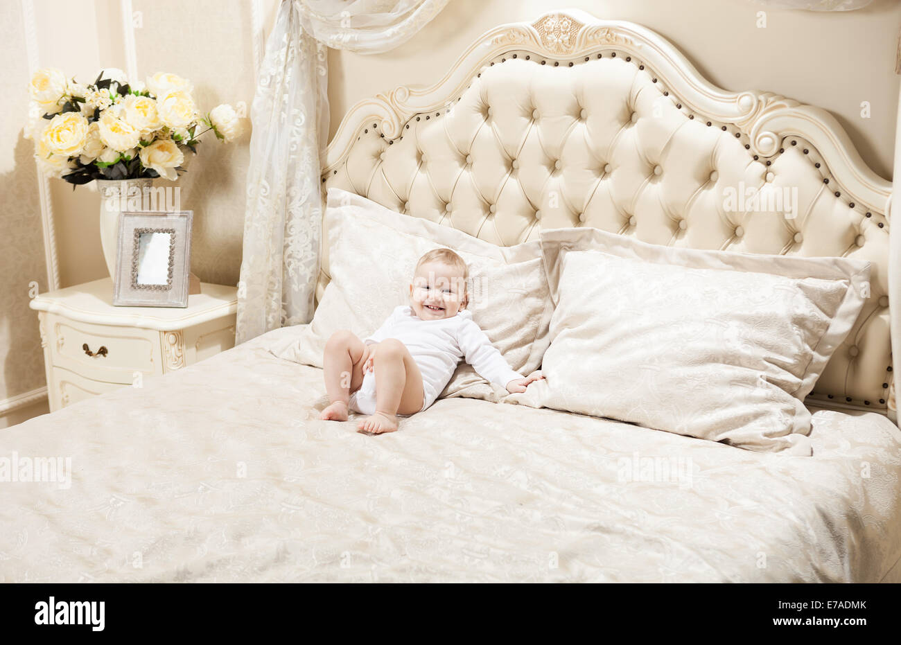 Little boy lying on bed at home and smiling Stock Photo