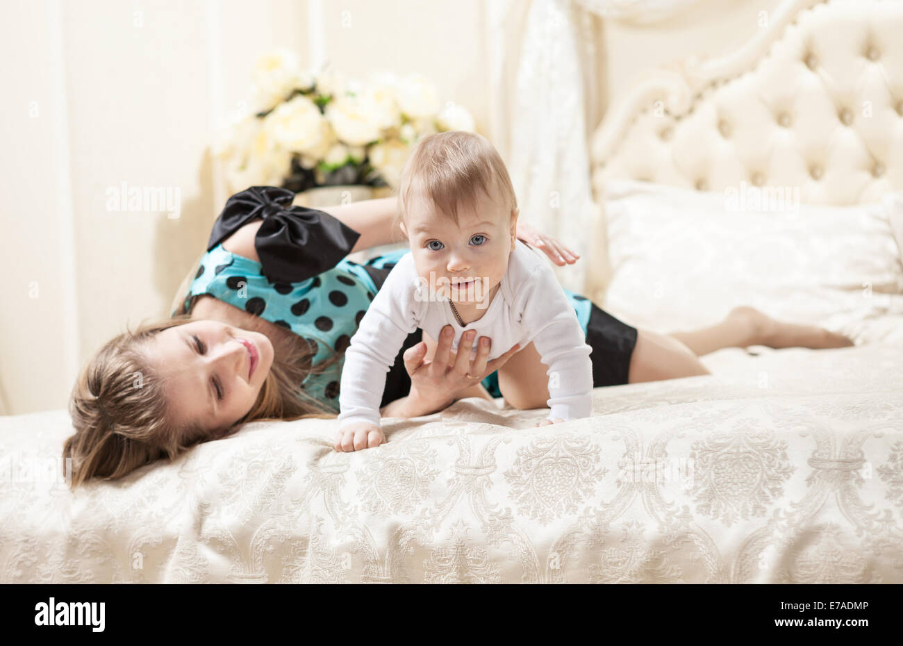 Young Caucasian mother and baby son on bed at home - Stock Image
