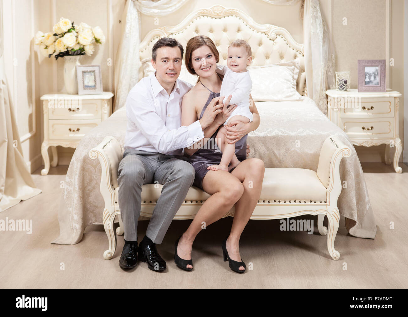Young happy family with a baby on bed at home Stock Photo