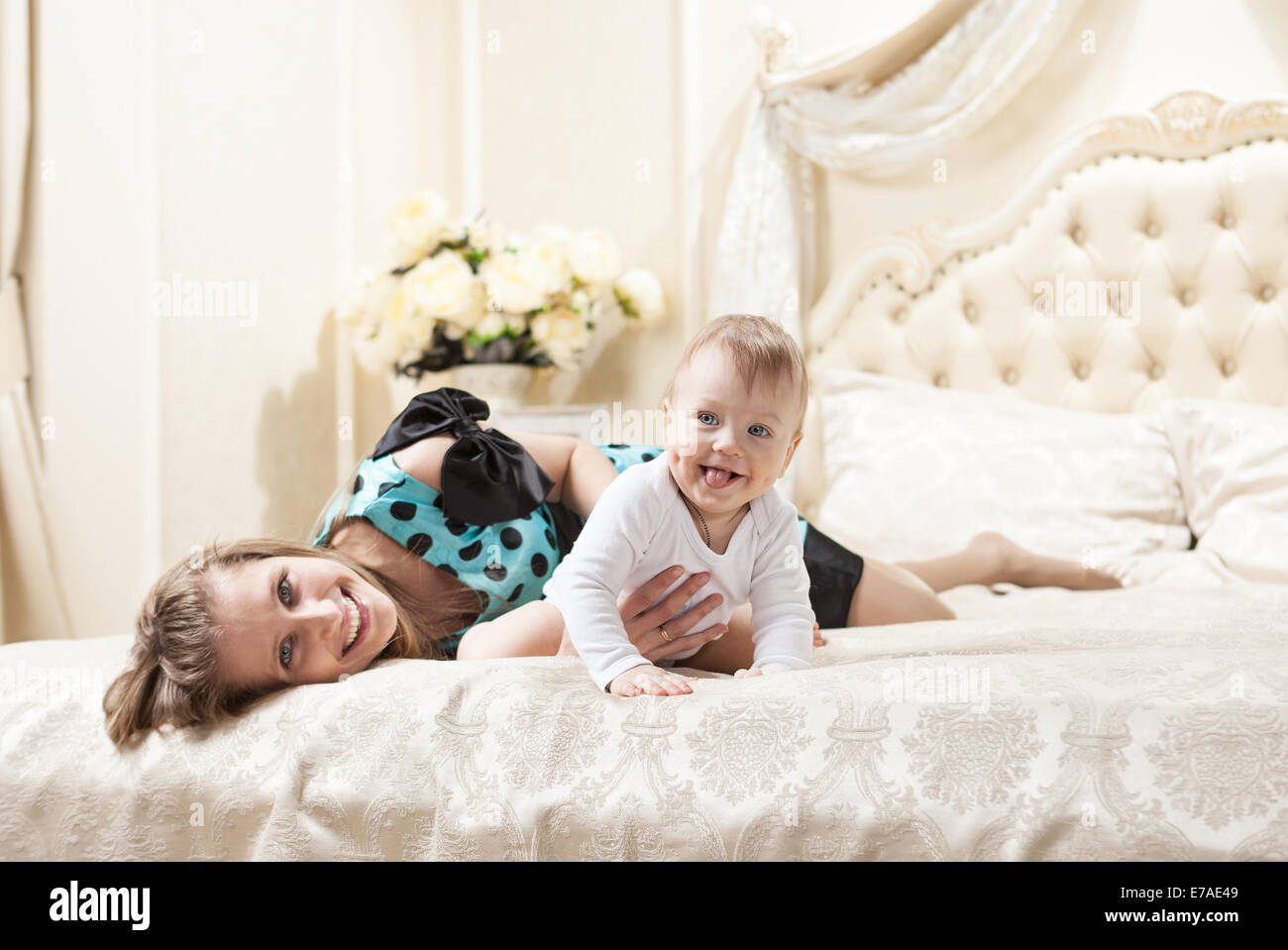 Young Caucasian mother and baby son on bed at home Stock Photo