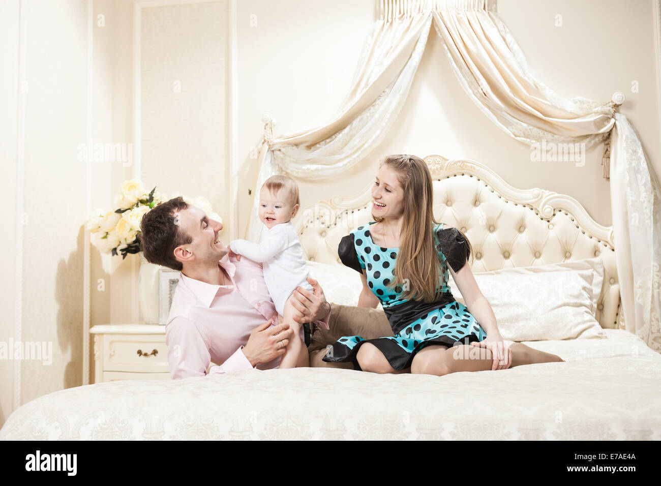 Young happy family with a baby on bed at home - Stock Image