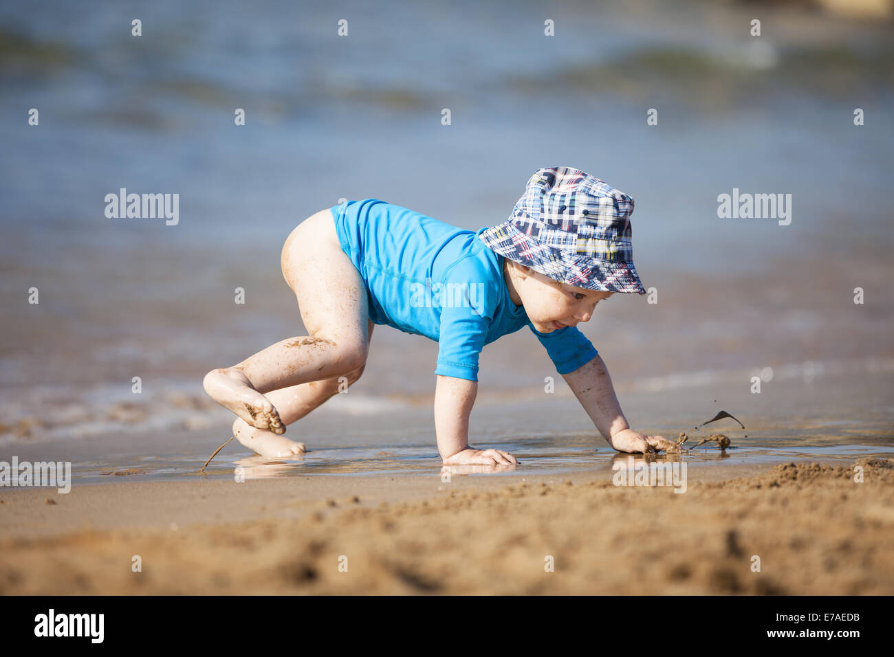 Small boy crawling towards water at the beach - Stock Image