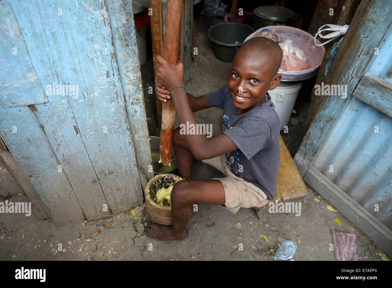 Boy pounding corn into flour in a mortar, making flatbread, Camp Icare for earthquake refugees, Fort National, Port - Stock Image