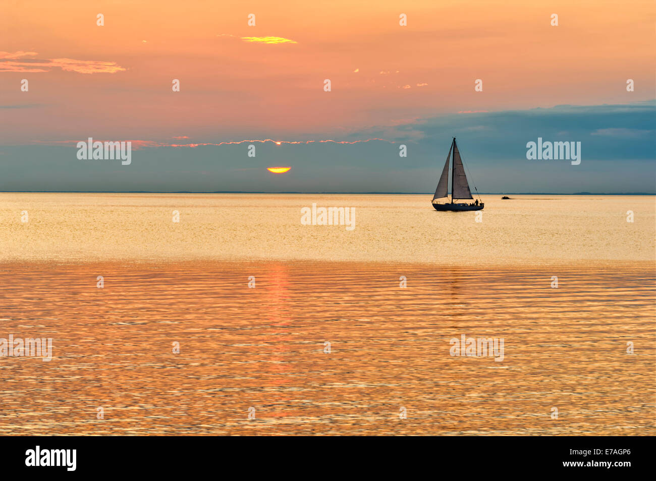 Silhouette  of a sailboat on calm waters, contrasting an orange and blue sunset sky on the Great Lakes, Green Bay, - Stock Image