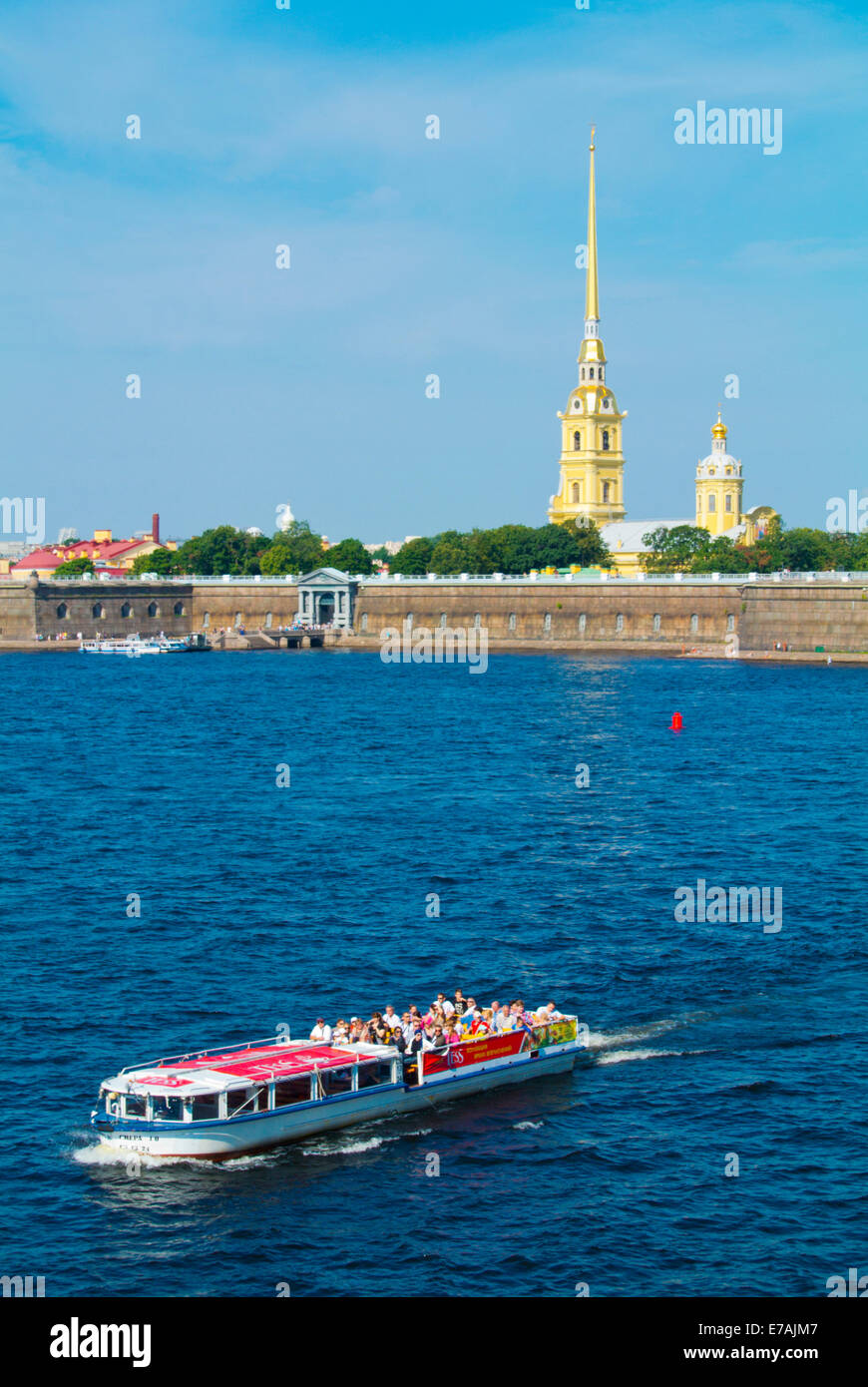 Sightseeing cruise tour boat on Neva river, with Peter and Paul fortress in background, Saint Petersburg, Russia, - Stock Image