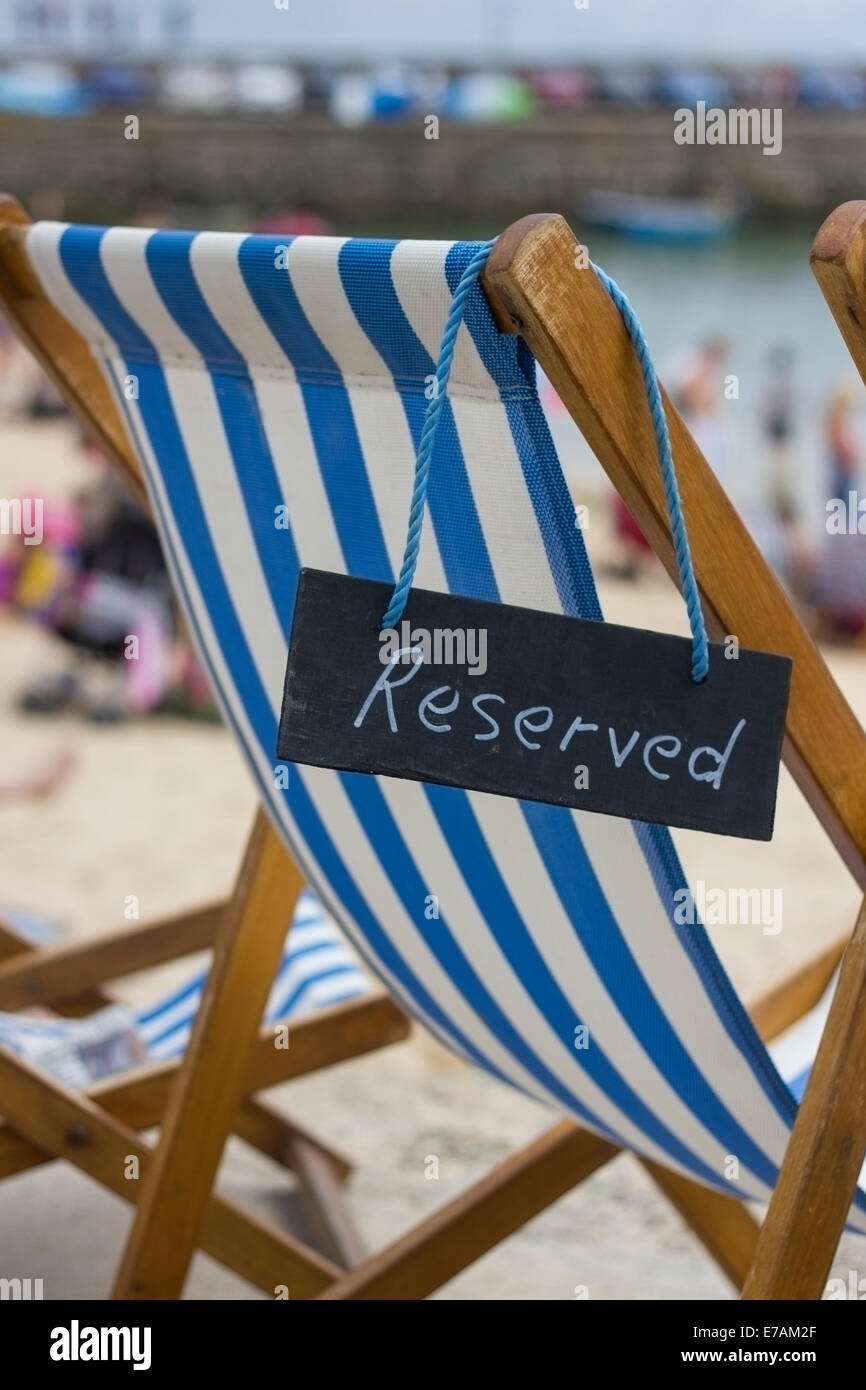 A deck chair with a reserved sign at Harbour beach in St Ives, Cornwall, England, UK - Stock Image