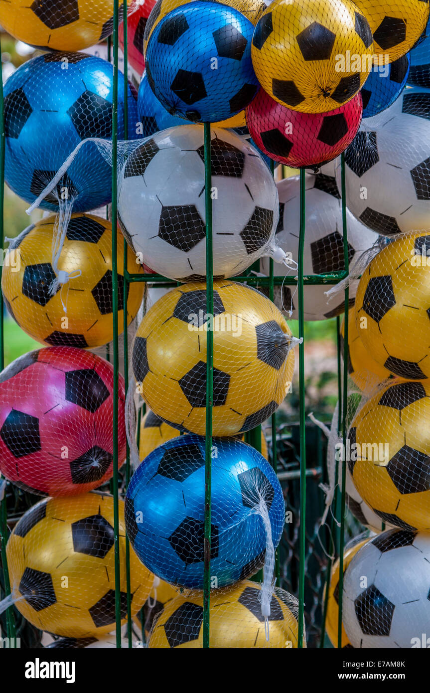 Colorful footballs/soccer balls are stacked in a cage ready for use. Stock Photo