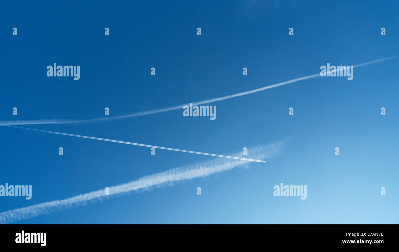 Parallel vapour trails being crossed by a jet plane in a blue sky above Great Britain KATHY DEWITT - Stock Image