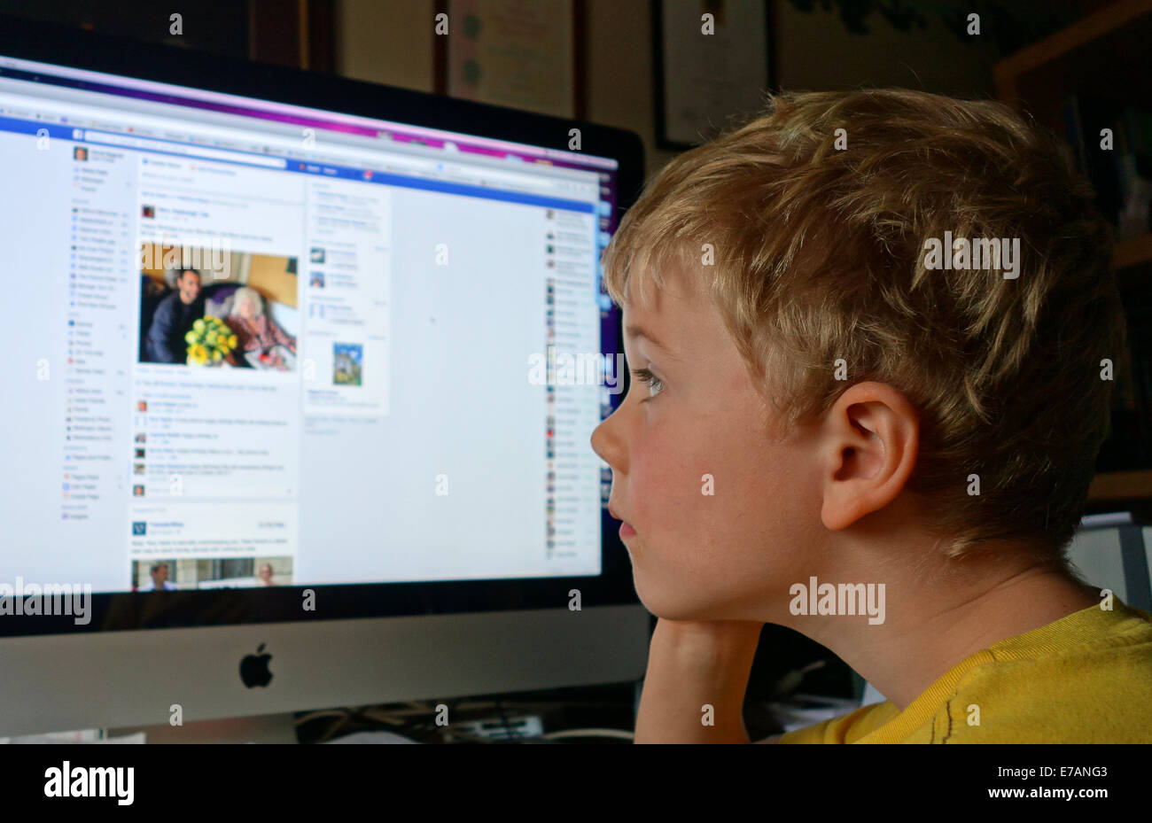 Child children boy looking at Facebook on home computer social media Uk - Stock Image