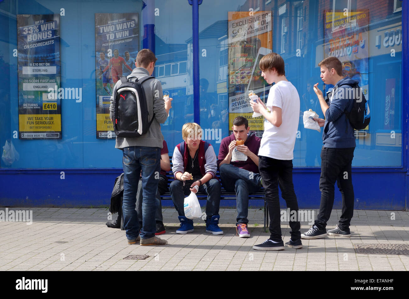 Teenage boys youths eating take away food lunchtime town centre street Wellington Shropshire Uk - Stock Image