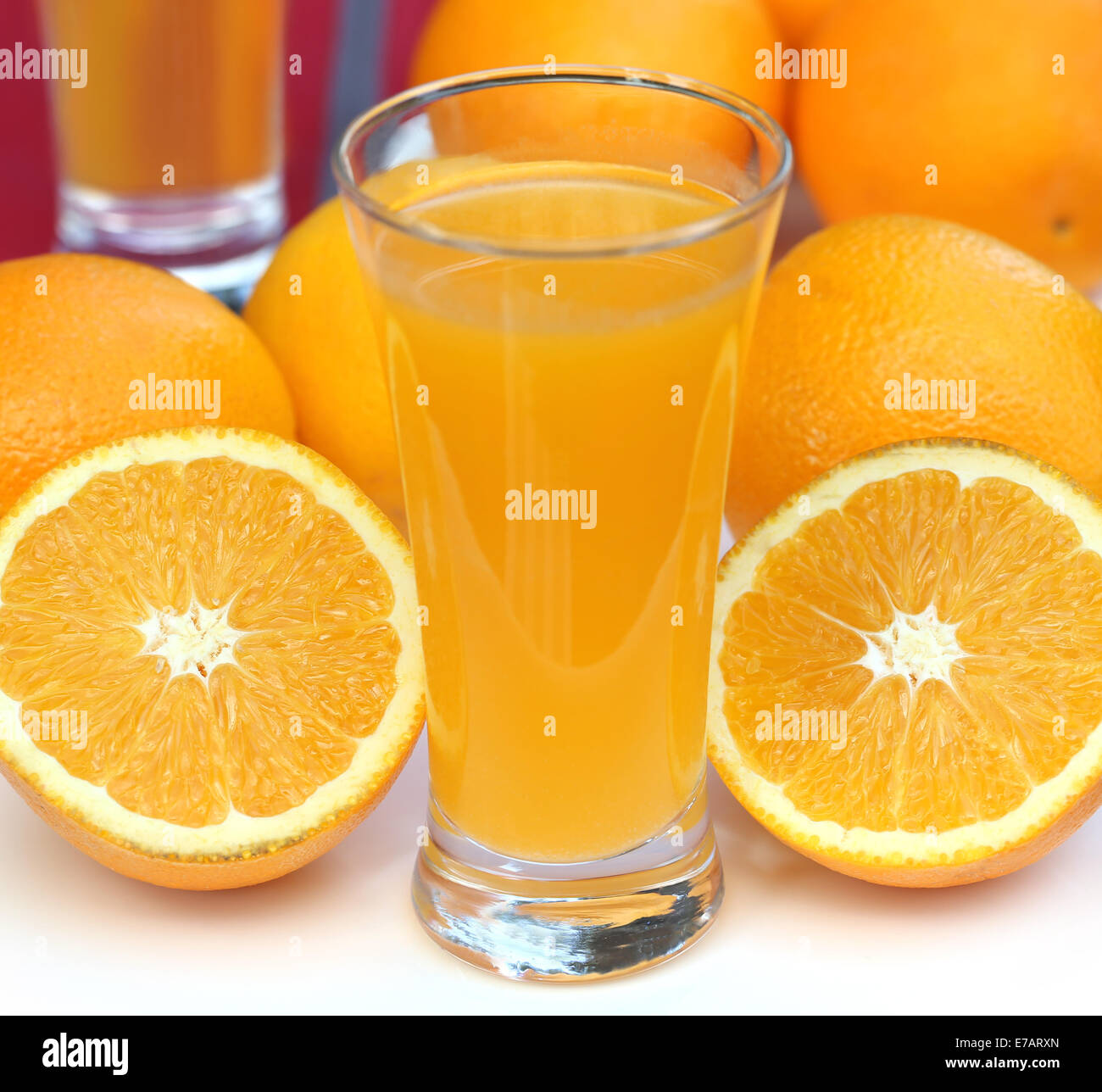 Oranges with glass of juice over white - Stock Image