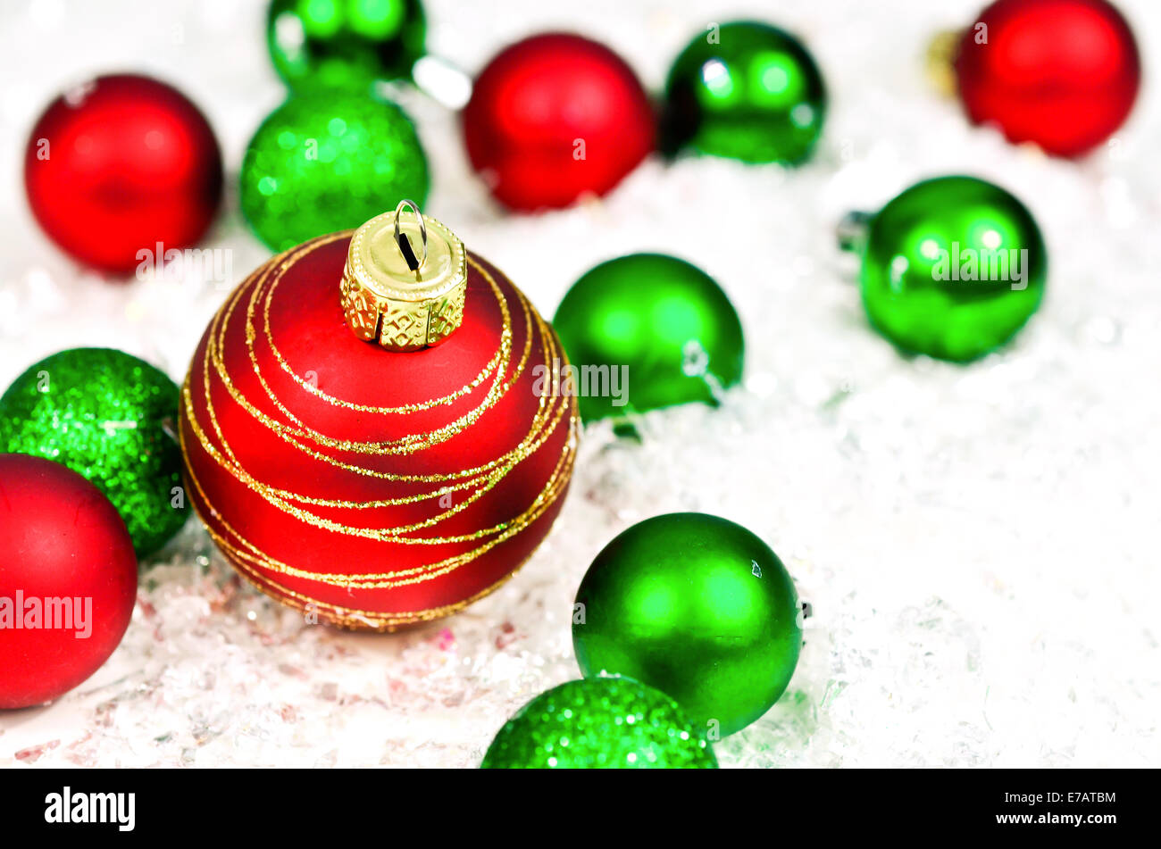 Red And Green Christmas Ornaments On Snow Background Stock Photo
