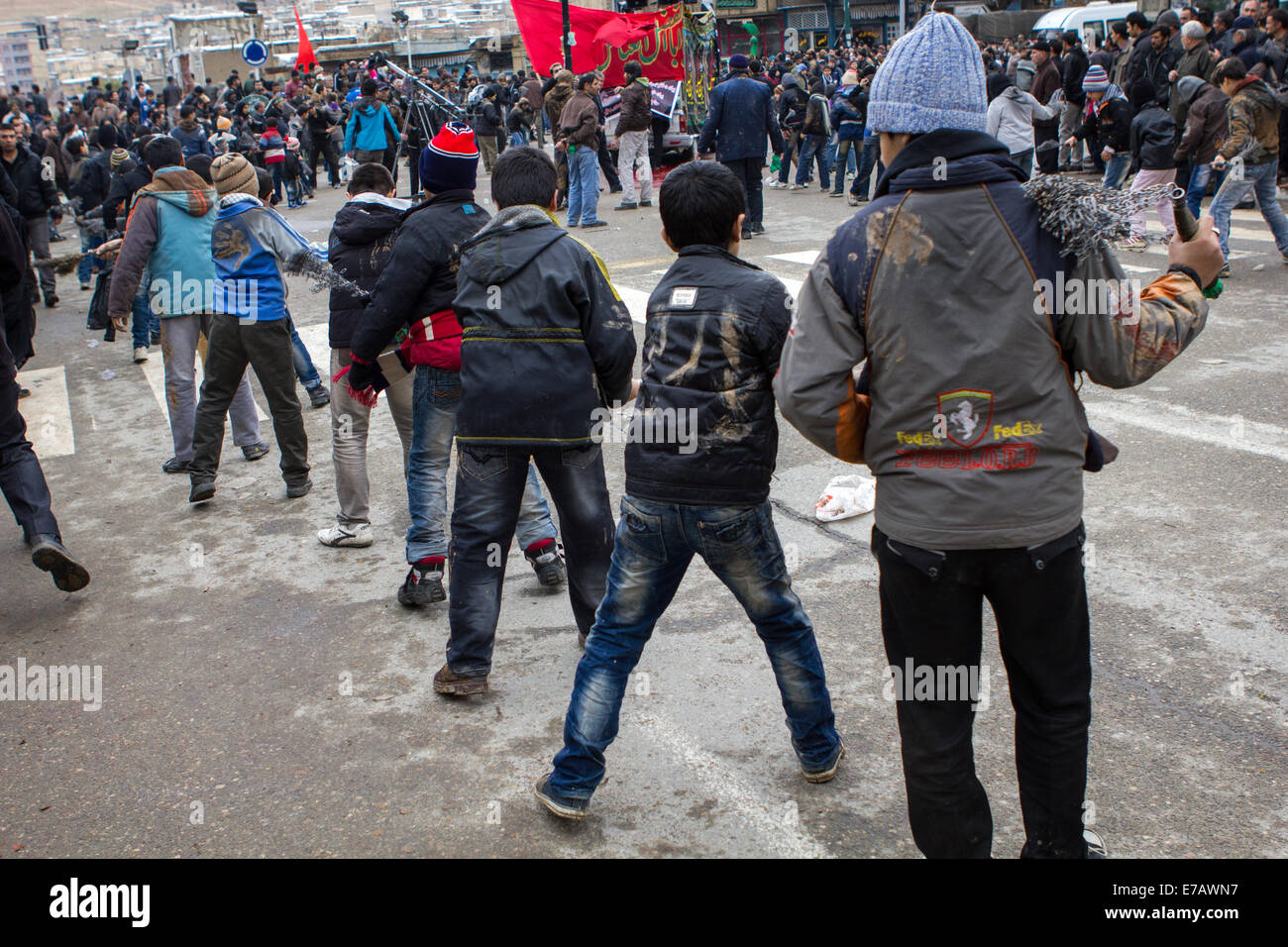 Shiite Muslim men and boys, chanting and self-flagellating during Ashura Day, on the streets of Bijar, Iran. - Stock Image