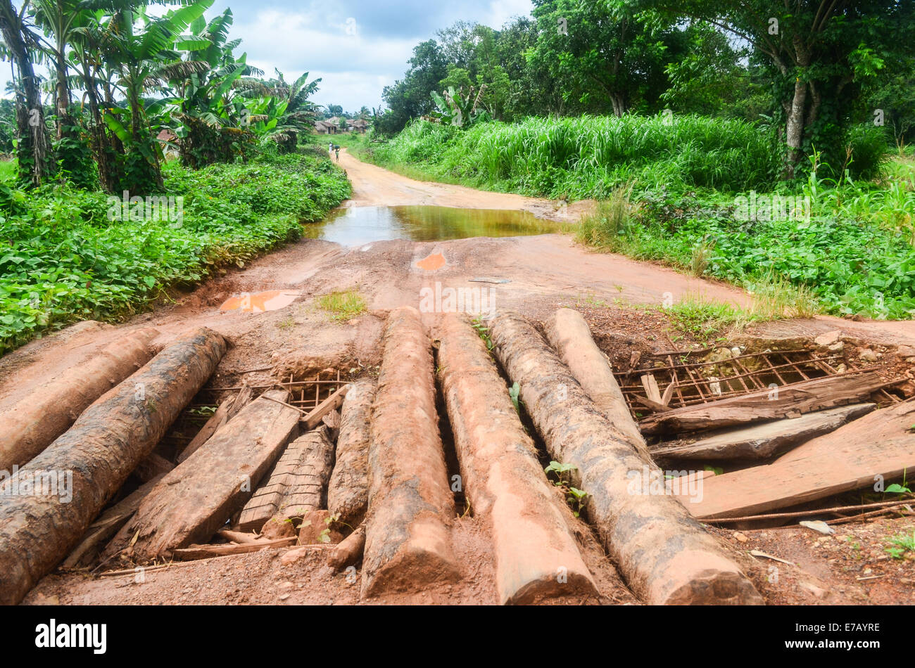 A makeshift bridge on the poor rural road network of Sierra Leone during the rainy season - Stock Image
