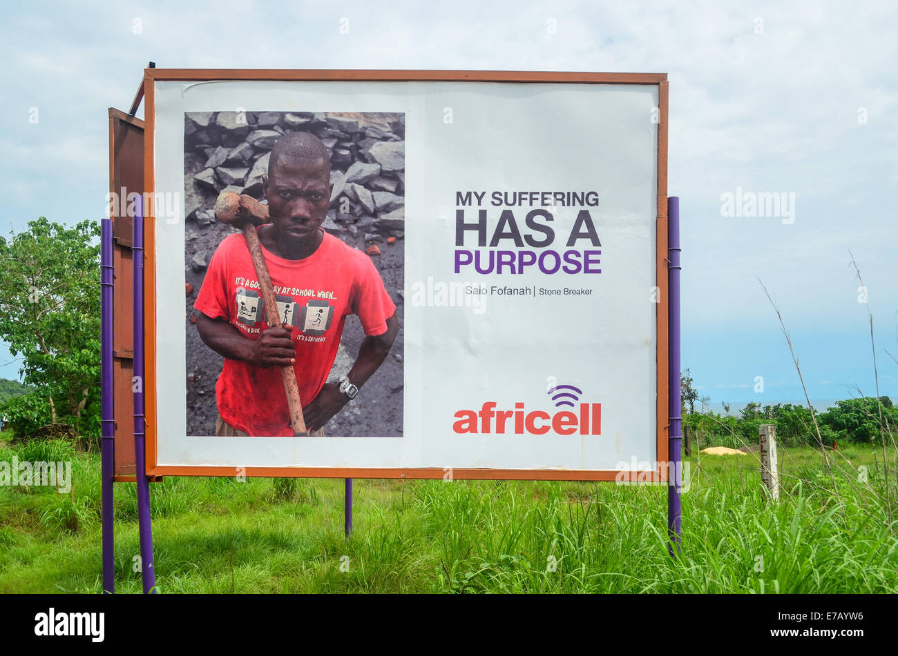 Africell (telephone operator) ad featuring a stone crusher, Sierra Leone - Stock Image