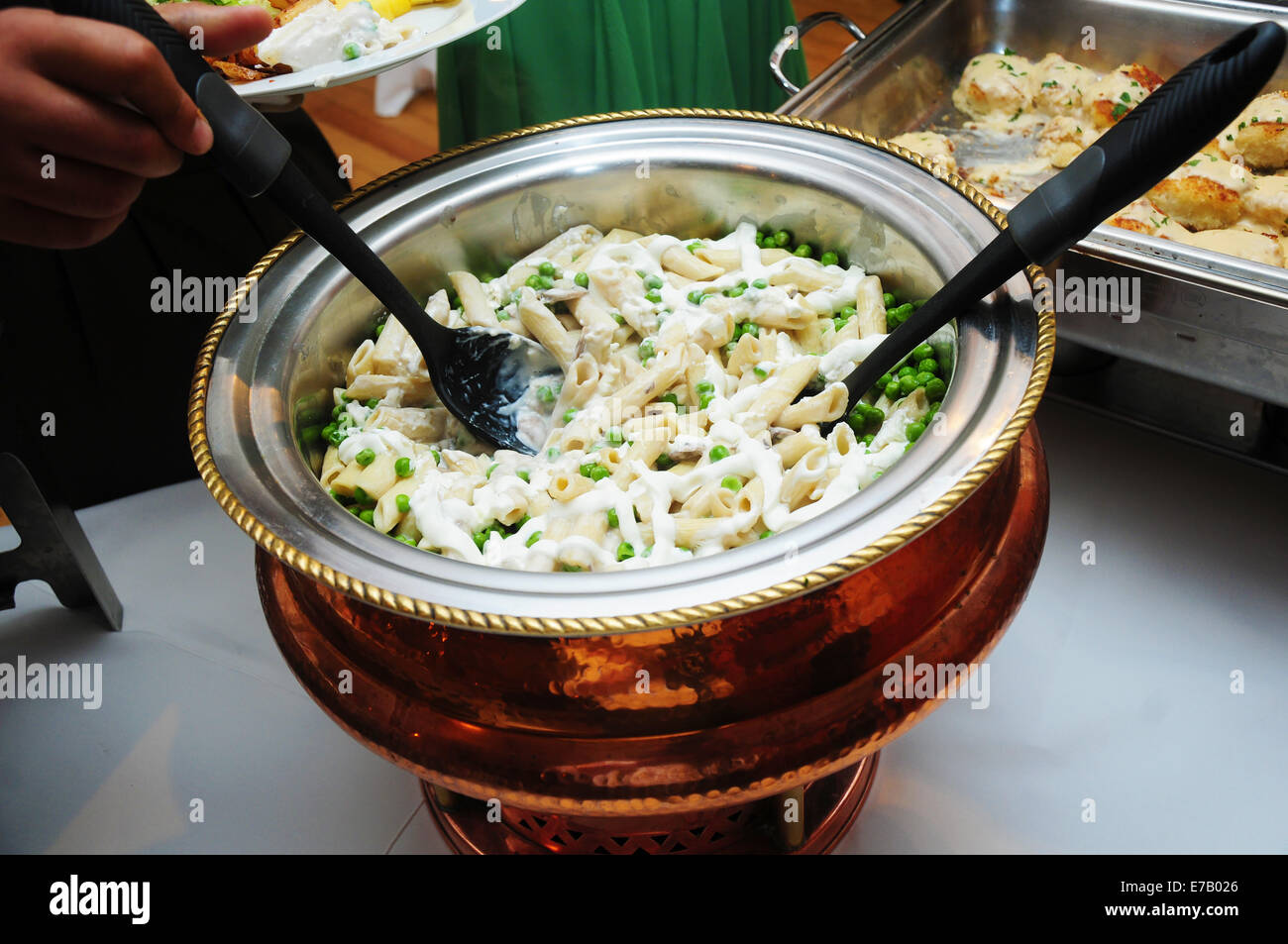 A large copper bowl of pasta and snow peas at a buffet. - Stock Image