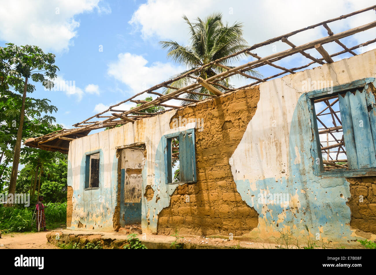 Woman standing by the ruins of a house in Sierra Leone, Africa - Stock Image