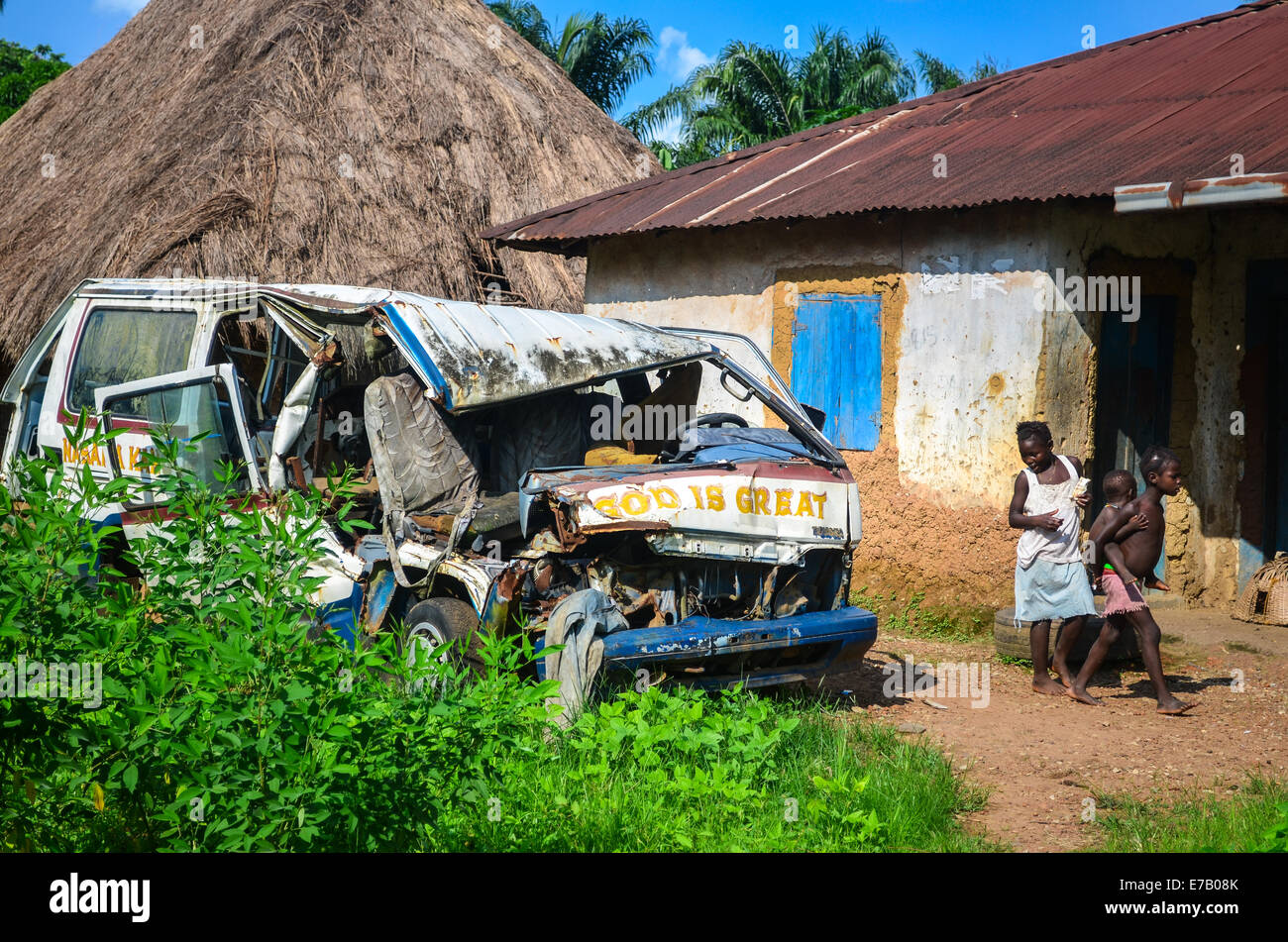Wrecked minibus reading 'GOD IS GREAT' on the roads of Sierra Leone, Africa - Stock Image