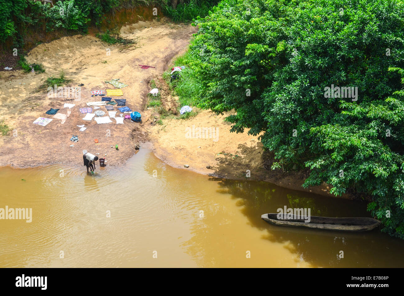 Woman doing laundry in a brown water river in Sierra Leone - Stock Image