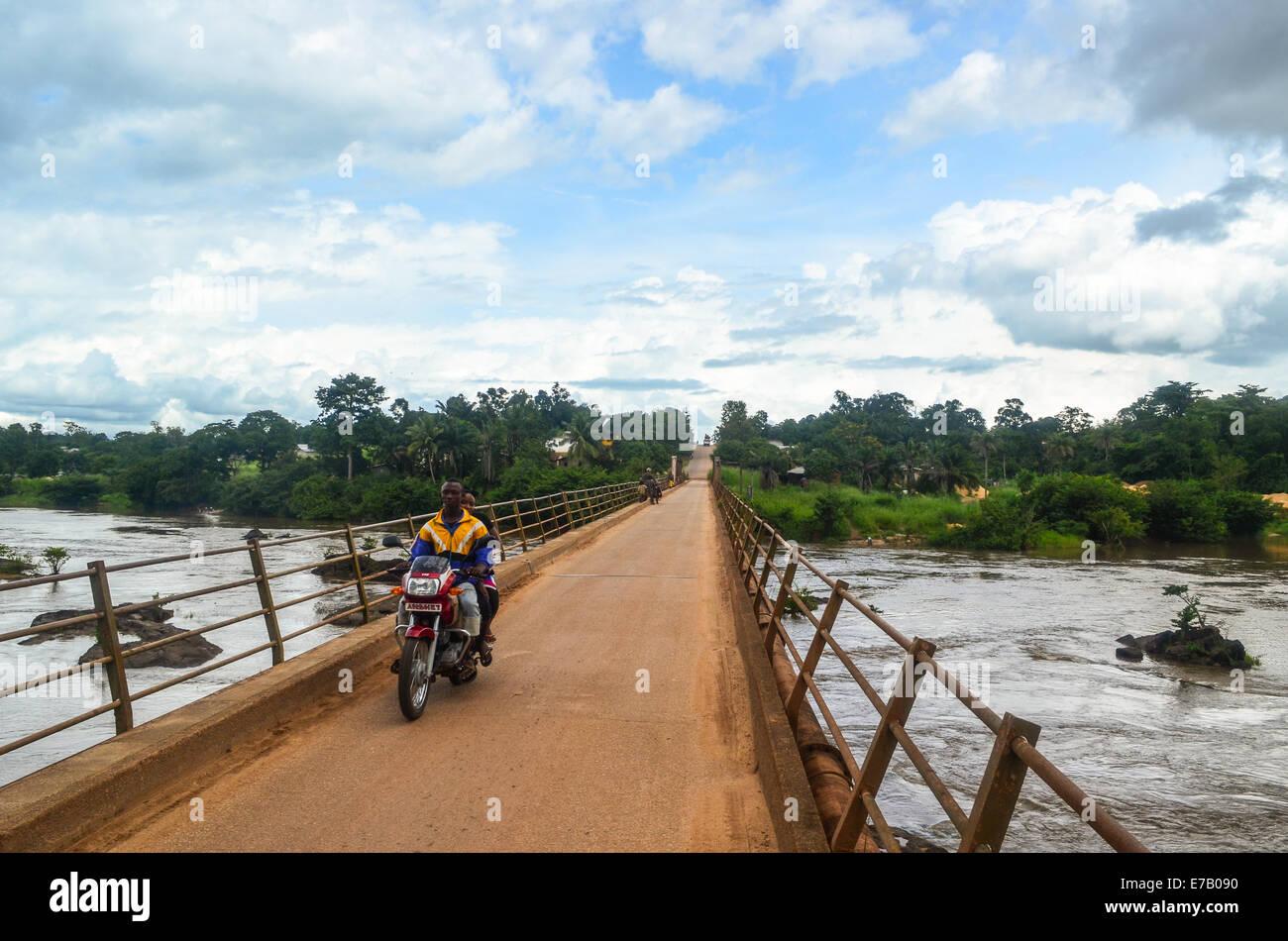 Motorbikers on a narrow bridge in the east of Sierra Leone, near Bo - Stock Image