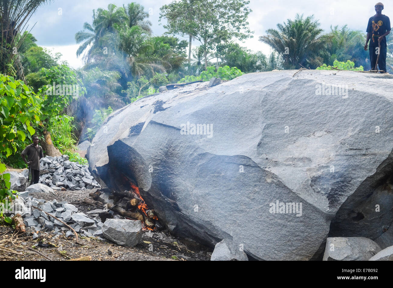 Stone-crushing people making a fire to break a stone down, Sierra Leone - Stock Image