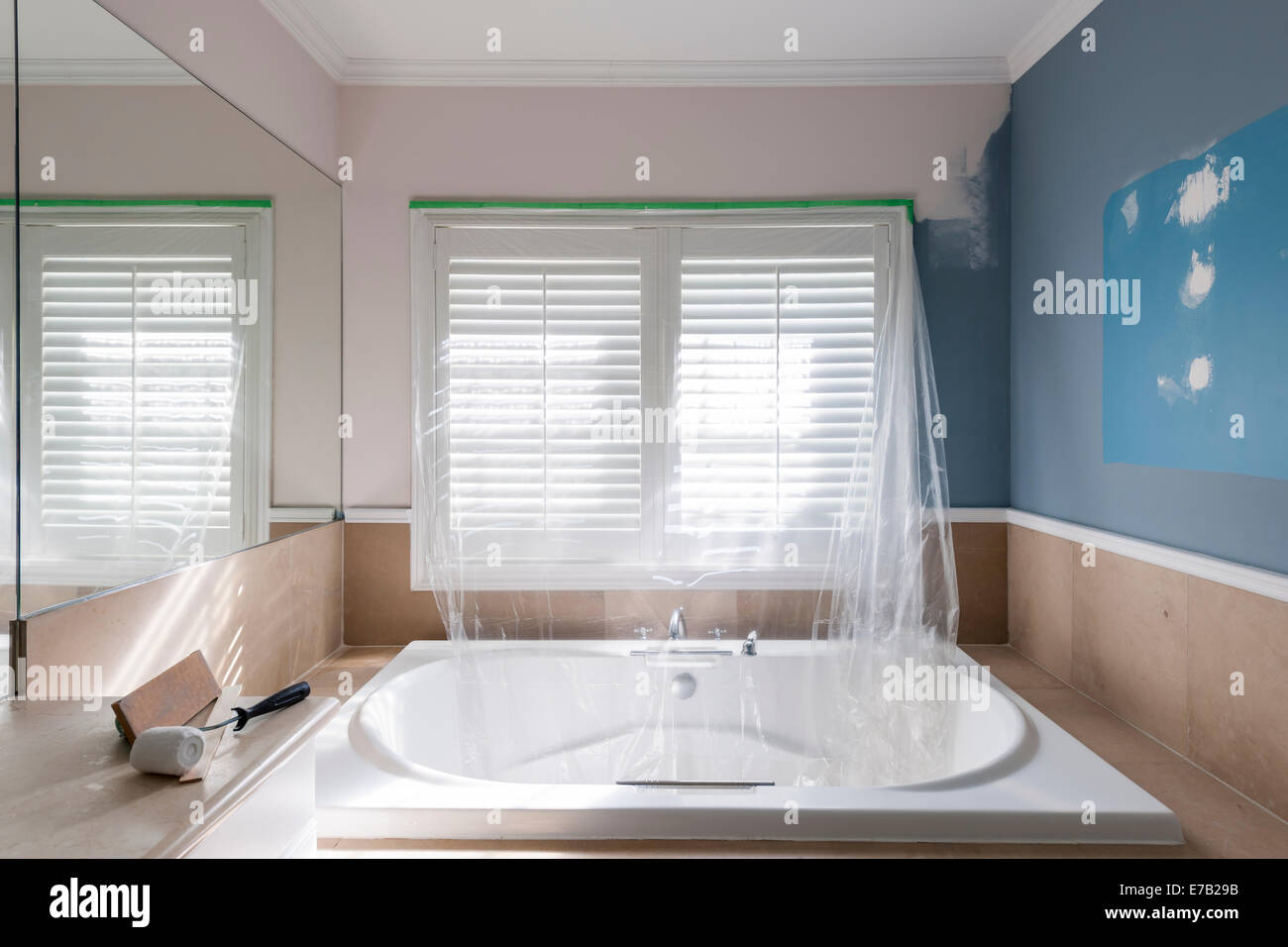Home renovation of residential bathroom with large tub showing paint ...