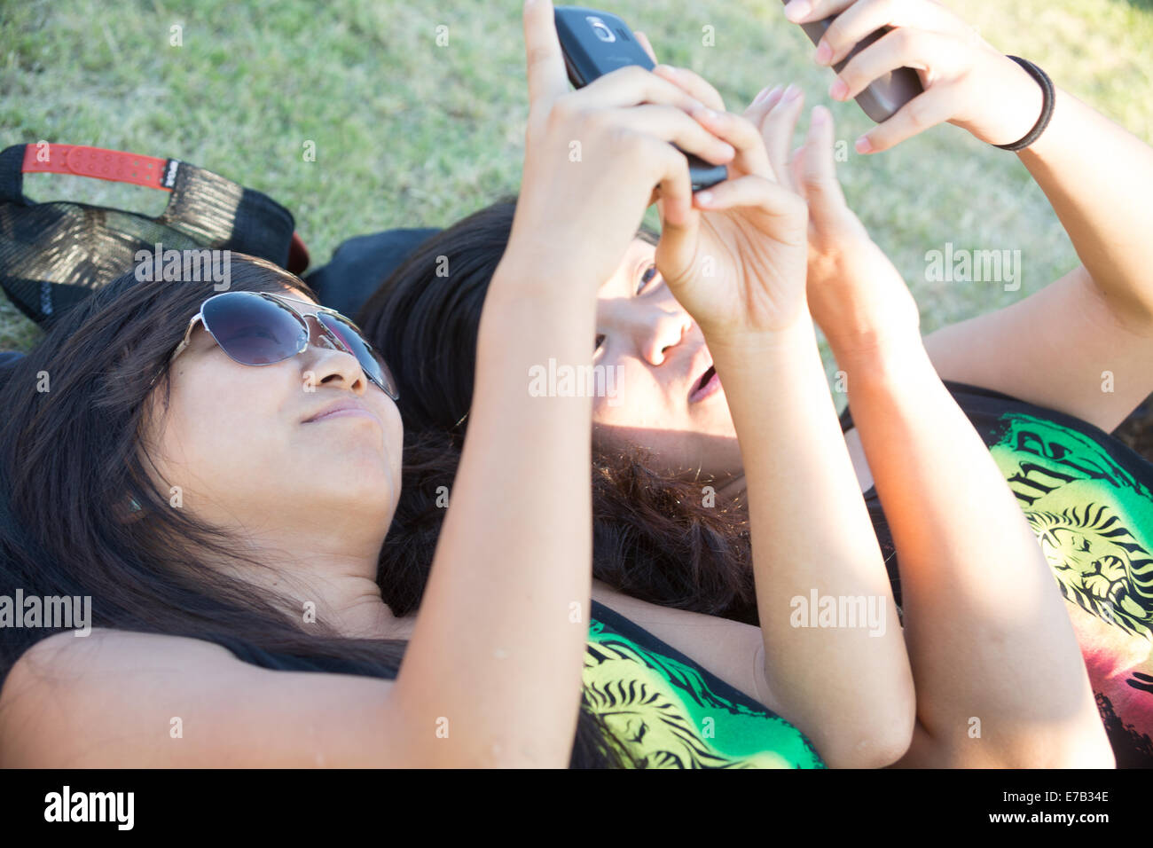 Two 20s Asian women lying on the grass looking at their cell phones - Stock Image