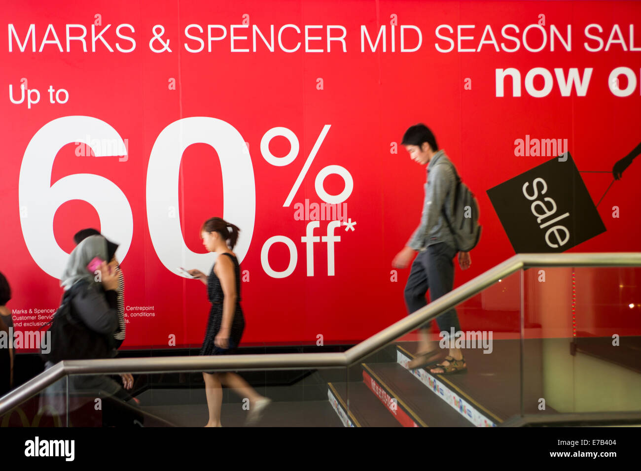 Shoppers climb a flight of stairs past an advertisement for a mid season  sale at a 3bf6506d17