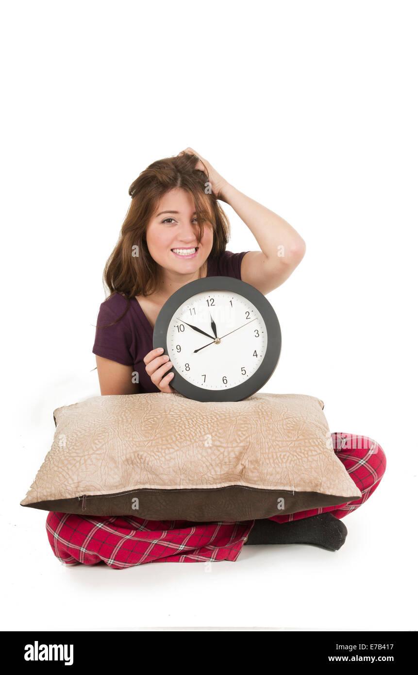 Cute young girl wearing pajamas holding big round clock - Stock Image